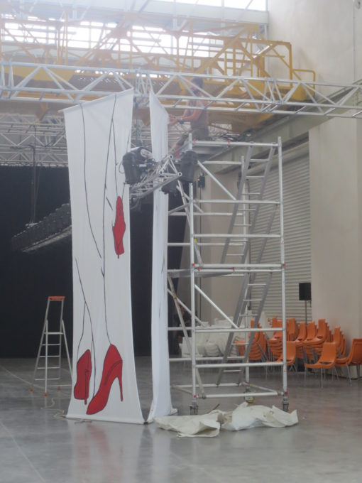 Salle du defile la grande halle préparation mise en scene grandes jambes talons rouge